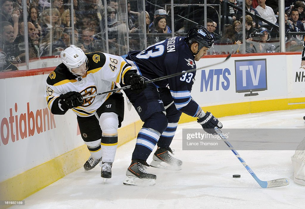 Dustin Byfuglien #33 of the Winnipeg Jets plays the puck away from Chris Bourque #48 of the Boston Bruins during third period action at the MTS Centre on February 17, 2013 in Winnipeg, Manitoba, Canada.