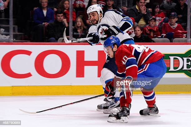 Dustin Byfuglien of the Winnipeg Jets shoots the puck in front of Nathan Beaulieu of the Montreal Canadiens during the NHL game at the Bell Centre on...
