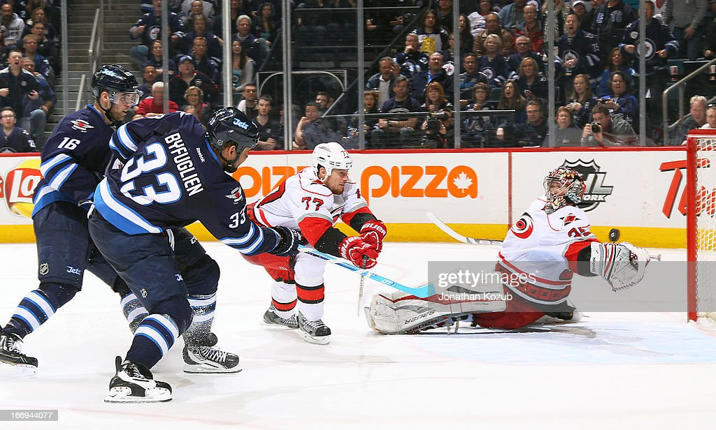 Dustin Byfuglien #33 of the Winnipeg Jets shoots the puck past the outstretched glove of goaltender Justin Peters #35 of the Carolina Hurricanes for the overtime winning goal at the MTS Centre on April 18, 2013 in Winnipeg, Manitoba, Canada.