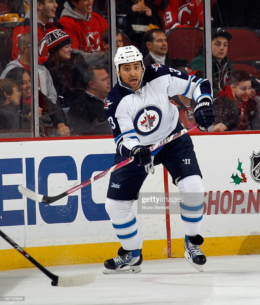 <a gi-track='captionPersonalityLinkClicked' href=/galleries/search?phrase=Dustin+Byfuglien&family=editorial&specificpeople=672505 ng-click='$event.stopPropagation()'>Dustin Byfuglien</a> #33 of the Winnipeg Jets skates against the New Jersey Devils at the Prudential Center on November 25, 2013 in Newark, New Jersey. The Jets defeated the Devils 3-1.