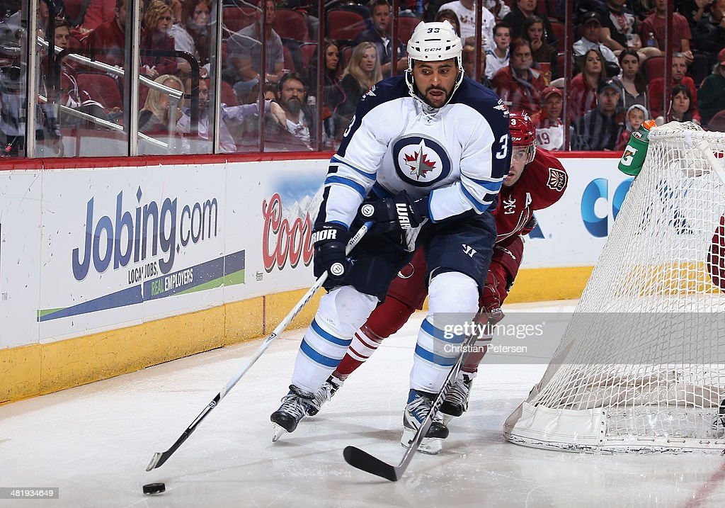 Dustin Byfuglien #33 of the Winnipeg Jets skates with the puck ahead of Keith Yandle #3 of the Phoenix Coyotes during the second period of the NHL game at Jobing.com Arena on April 1, 2014 in Glendale, Arizona. The Jets defeated the Coyotes 2-1 in an overtime shootout.