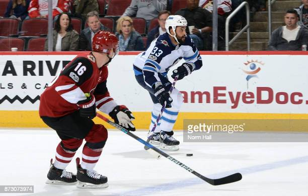 Dustin Byfuglien of the Winnipeg Jets skates with the puck ahead of Max Domi of the Arizona Coyotes during the first period at Gila River Arena on...