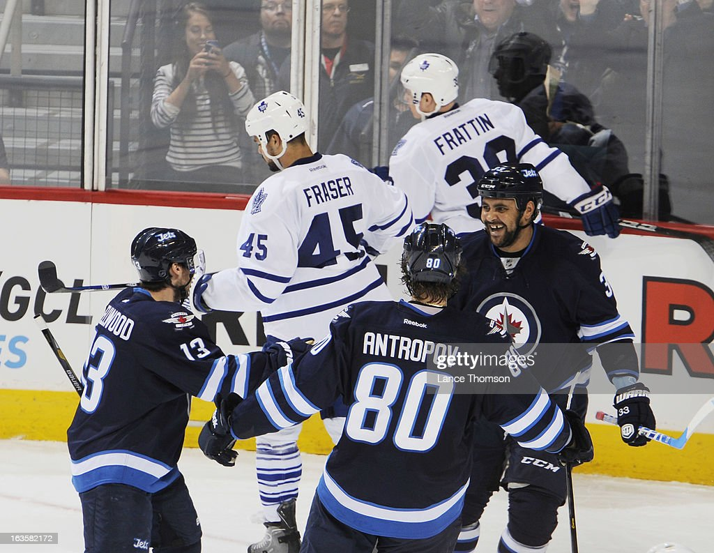 <a gi-track='captionPersonalityLinkClicked' href=/galleries/search?phrase=Dustin+Byfuglien&family=editorial&specificpeople=672505 ng-click='$event.stopPropagation()'>Dustin Byfuglien</a> #33 of the Winnipeg Jets smiles as he celebrates a second period goal against the Toronto Maple Leafs with teammates <a gi-track='captionPersonalityLinkClicked' href=/galleries/search?phrase=Kyle+Wellwood&family=editorial&specificpeople=577984 ng-click='$event.stopPropagation()'>Kyle Wellwood</a> #13 and <a gi-track='captionPersonalityLinkClicked' href=/galleries/search?phrase=Nik+Antropov&family=editorial&specificpeople=202953 ng-click='$event.stopPropagation()'>Nik Antropov</a> #80 at the MTS Centre on March 12, 2013 in Winnipeg, Manitoba, Canada.