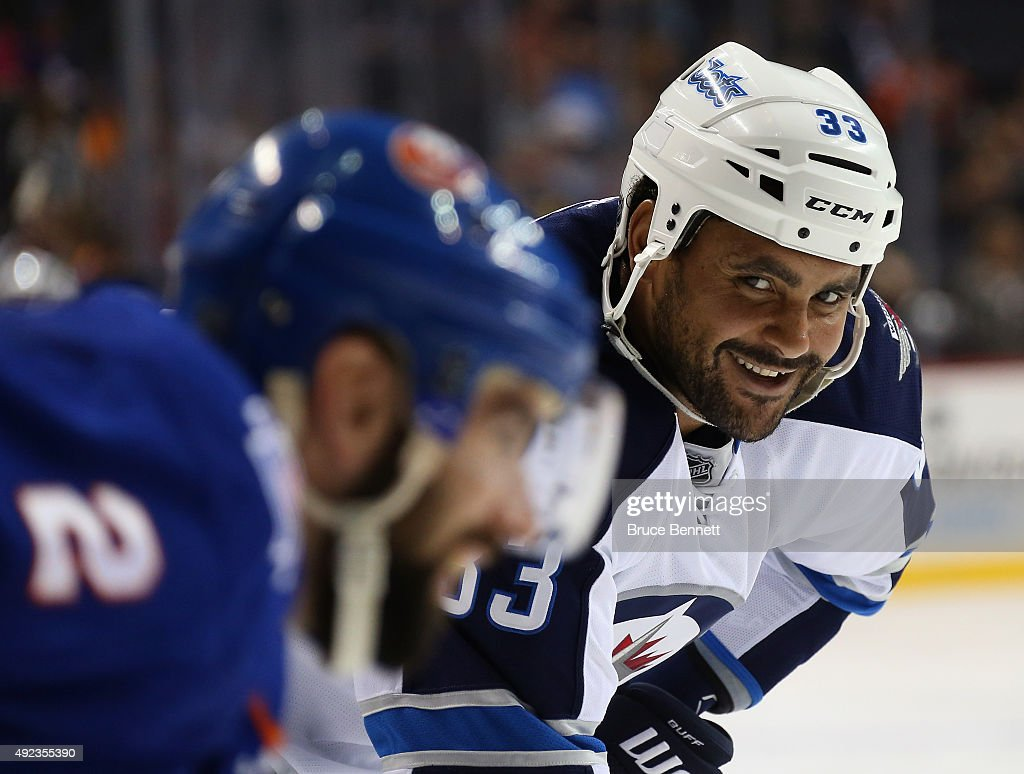 Dustin Byfuglien #33 of the Winnipeg Jets speaks to Nick Leddy #2 of the New York Islanders during the third period at the Barclays Center on October 12, 2015 in the Brooklyn borough of New York City. The Islanders defeated the Jets 4-2.
