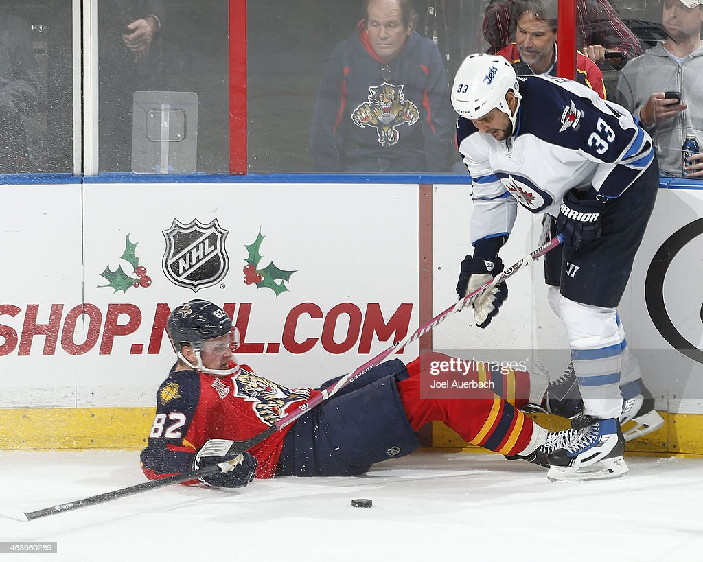 Dustin Byfuglien #33 of the Winnipeg Jets takes the puck from Tomas Kopecky #82 of the Florida Panthers after checking him in the third period at the BB&T Center on December 5, 2013 in Sunrise, Florida. The Panthers defeated the Jets 5-2.