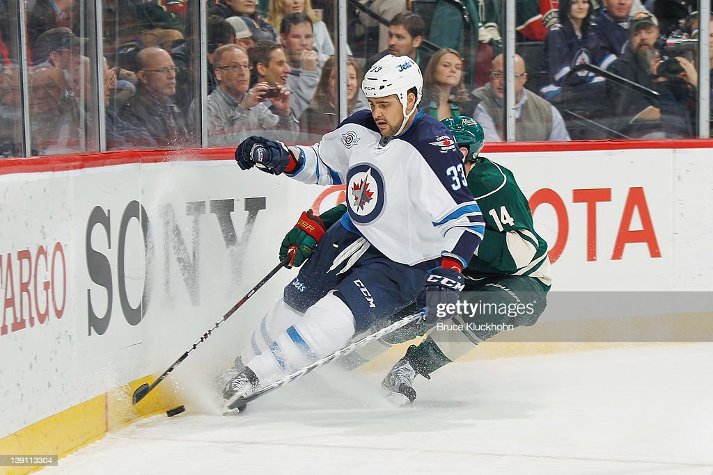 <a gi-track='captionPersonalityLinkClicked' href=/galleries/search?phrase=Dustin+Byfuglien&family=editorial&specificpeople=672505 ng-click='$event.stopPropagation()'>Dustin Byfuglien</a> #33 of the Winnipeg Jets touches up the puck for an icing call despite the efforts of <a gi-track='captionPersonalityLinkClicked' href=/galleries/search?phrase=Darroll+Powe&family=editorial&specificpeople=4527845 ng-click='$event.stopPropagation()'>Darroll Powe</a> #14 of the Minnesota Wild during the game at the Xcel Energy Center on February 16, 2012 in St. Paul, Minnesota.