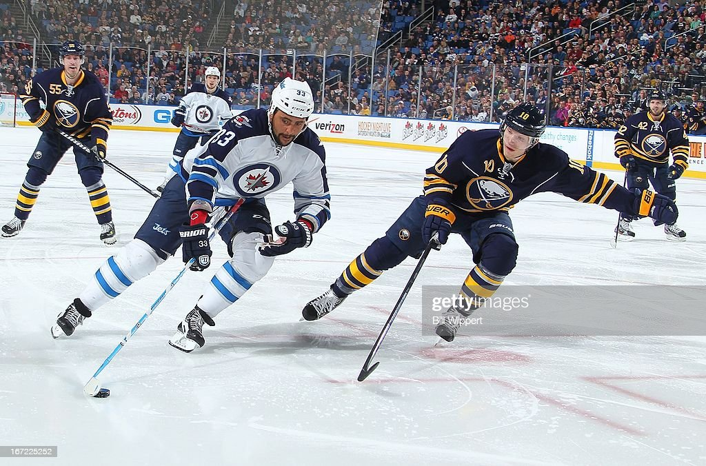 Dustin Byfuglien #33 of the Winnipeg Jets tries to get by Christian Ehrhoff #10 of the Buffalo Sabres on April 22, 2013 at the First Niagara Center in Buffalo, New York.