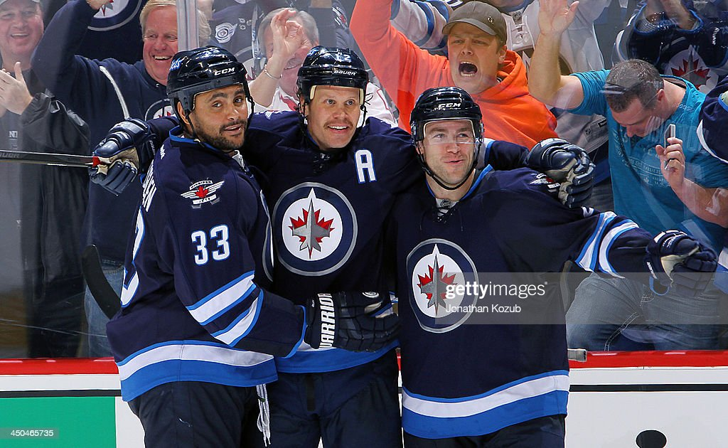 <a gi-track='captionPersonalityLinkClicked' href=/galleries/search?phrase=Dustin+Byfuglien&family=editorial&specificpeople=672505 ng-click='$event.stopPropagation()'>Dustin Byfuglien</a> #33, <a gi-track='captionPersonalityLinkClicked' href=/galleries/search?phrase=Olli+Jokinen&family=editorial&specificpeople=202946 ng-click='$event.stopPropagation()'>Olli Jokinen</a> #12 and <a gi-track='captionPersonalityLinkClicked' href=/galleries/search?phrase=Grant+Clitsome&family=editorial&specificpeople=4596638 ng-click='$event.stopPropagation()'>Grant Clitsome</a> #24 of the Winnipeg Jets celebrate a third period goal against the Calgary Flames at the MTS Centre on November 18, 2013 in Winnipeg, Manitoba, Canada.
