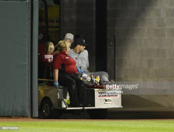 Dustin Fowler of the New York Yankees is taken off the field in a cart after trying to catch a foul ball against the Chicago White Sox during the...