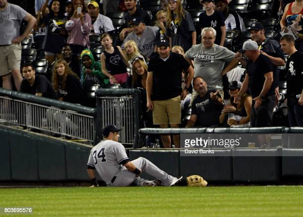Dustin Fowler of the New York Yankees sits on the ground after trying to catch a foul ball hit by Jose Abreu of the Chicago White Sox Fowler had to...