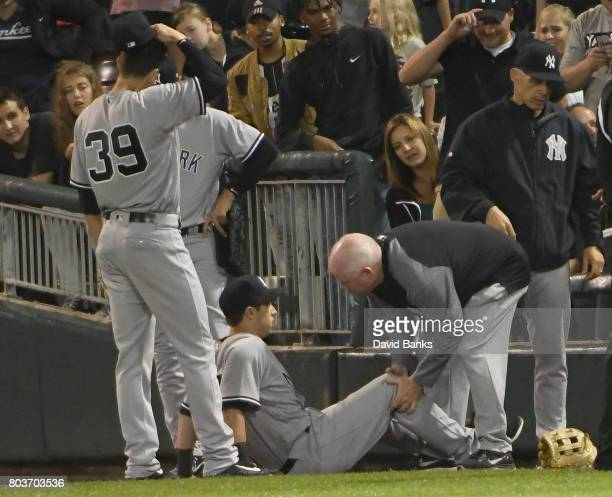 Dustin Fowler of the New York Yankees sits on the ground as the trainer looks at his leg after trying to catch a foul ball hit by Jose Abreu of the...