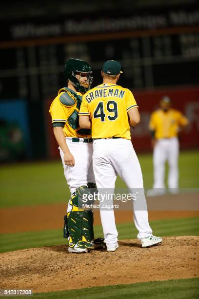 Dustin Garneau and Kendall Graveman of the Oakland Athletics talk on the mound during the game against the Seattle Mariners at the Oakland Alameda...