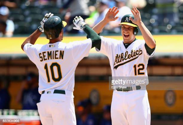 Dustin Garneau congratulates Marcus Semien of the Oakland Athletics after he hit a tworun home run in the third inning against the Kansas City Royals...