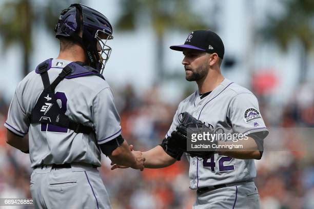 Dustin Garneau of the Colorado Rockies congratulates starting pitcher Tyler Chatwood of the Colorado Rockies after a win and a complete game shutout...