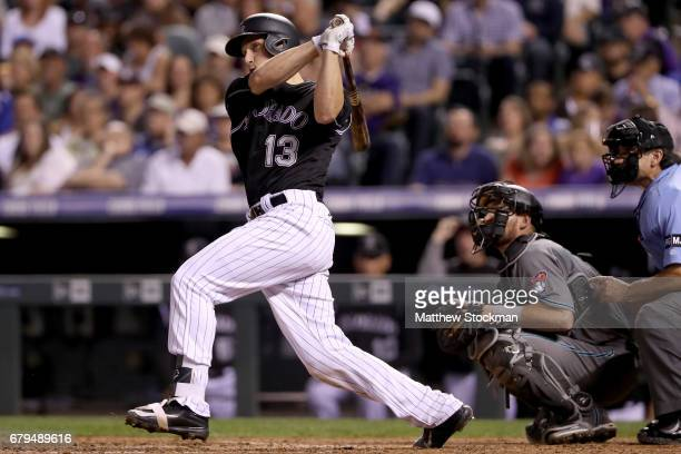 Dustin Garneau of the Colorado Rockies hits a RBI double in the seventh inning against the Arizona Diamondbacks at Coors Field on May 5 2017 in...