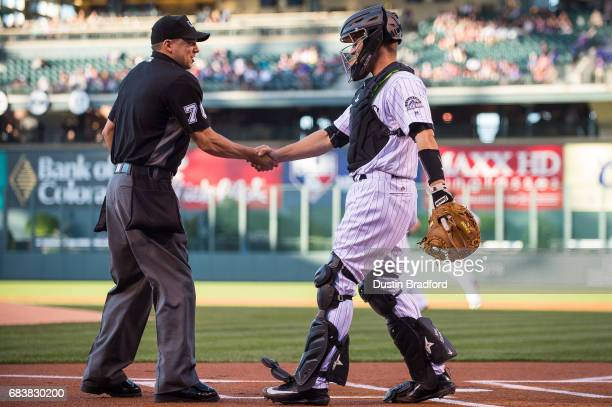 Dustin Garneau of the Colorado Rockies shakes hands with umpire Adam Hamari before a game between the Colorado Rockies and the Los Angeles Dodgers at...
