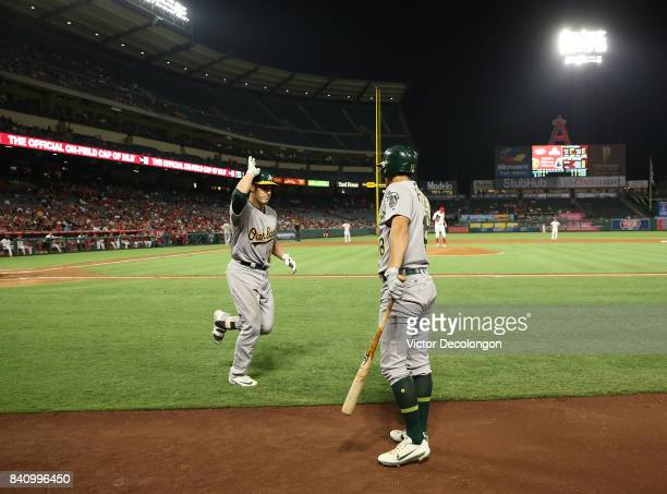 Dustin Garneau of the Oakland Athletics celebrates with teammate Chad Pinder on his way to the dugout after Garneau scored on his solo homerun during...