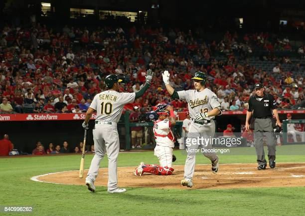 Dustin Garneau of the Oakland Athletics gets a high five from teammate Marcus Semien after Garneau scored on his solo homerun as catcher Martin...