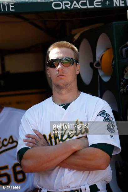 Dustin Garneau of the Oakland Athletics stands in the dugout during the game against the Kansas City Royals at the Oakland Alameda Coliseum on August...
