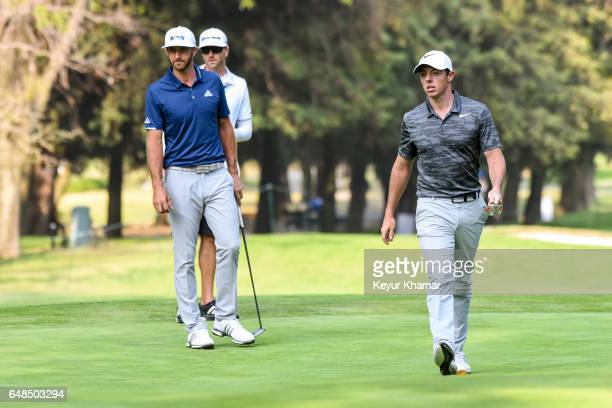 Dustin Johnson and his caddie Austin Johnson watch the putting line of Rory McIlroy of Northern Ireland on the 16th hole green during the final round...