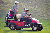 Dustin Johnson and Jordan Spieth of the United States team get a ride from Jim Furyk during a practice round prior to the start of The Presidents Cup...