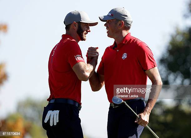 Dustin Johnson and Matt Kuchar of the United States react after a putt on the 14th green to end the match during morning foursome matches of the 2016...