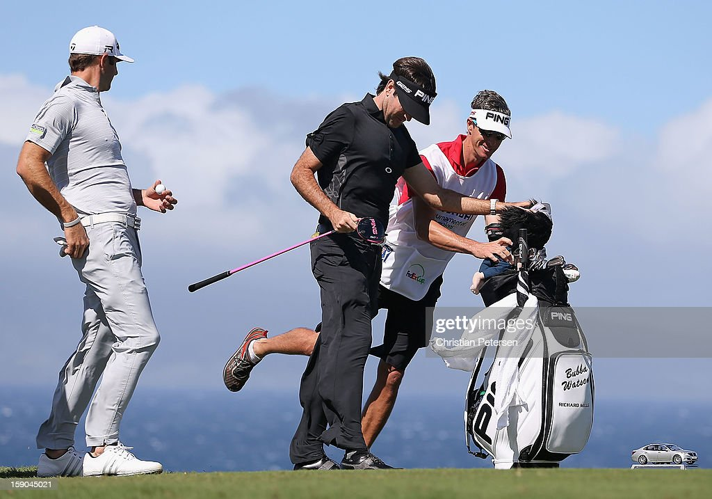 Dustin Johnson, Bubba Watson and caddie Ted Scott lean into the wind on the 10th hole tee box during the replay of the first round of the Hyundai Tournament of Champions at the Plantation Course on January 6, 2013 in Kapalua, Hawaii.
