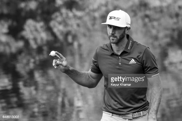 Dustin Johnson celebrates and waves his ball to fans after making a par putt on the 17th hole green during the final round of the World Golf...