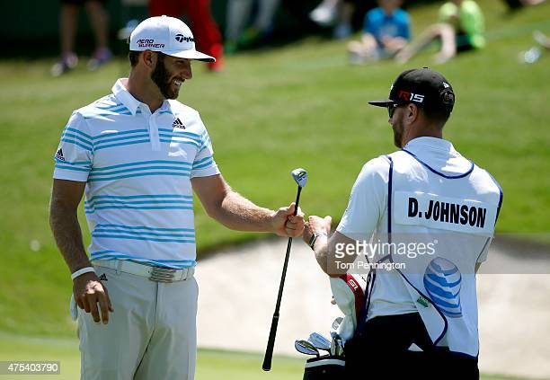 Dustin Johnson celebrates with his caddie after making birdie on the first hole during the Final Round of the ATT Byron Nelson at the TPC Four...