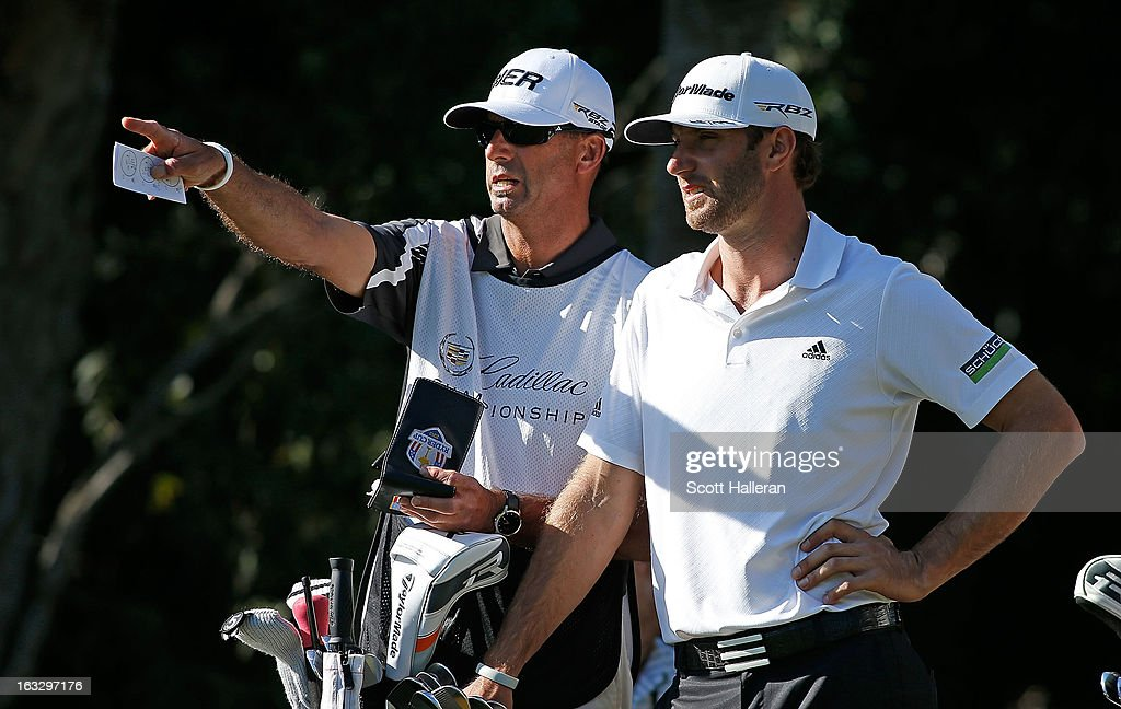 Dustin Johnson chats with his caddie Bobby Brown on the 16th tee during the first round of the WGC-Cadillac Championship at the Trump Doral Golf Resort & Spa in Miami, Florida.