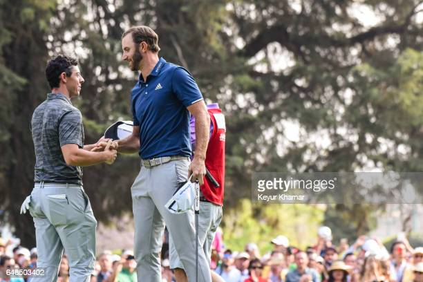 Dustin Johnson greets Rory McIlroy of Northern Ireland after his victory on the 18th hole green during the final round of the World Golf...
