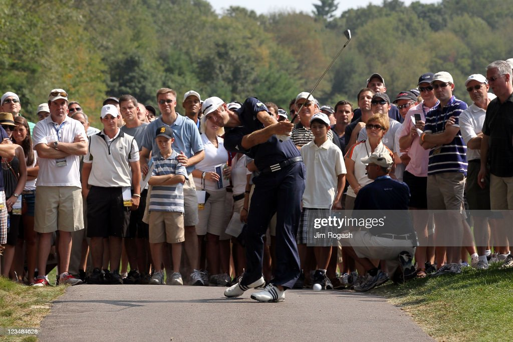 Dustin Johnson hits a shot off of the cart path along the seventh hole as the gallery watches during the second round of the Deutsche Bank Championship at TPC Boston on September 3, 2011 in Norton, Massachusetts.