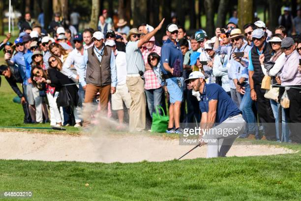 Dustin Johnson hits out of a greenside bunker as fans watch on the 15th hole green during the final round of the World Golf ChampionshipsMexico...