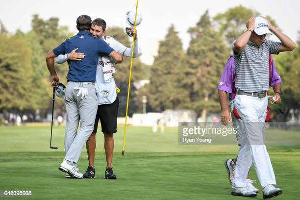 Dustin Johnson hugs his brother and caddie Austin Johnson as Justin Thomas walks off the green following Johnson's victory during the final round of...