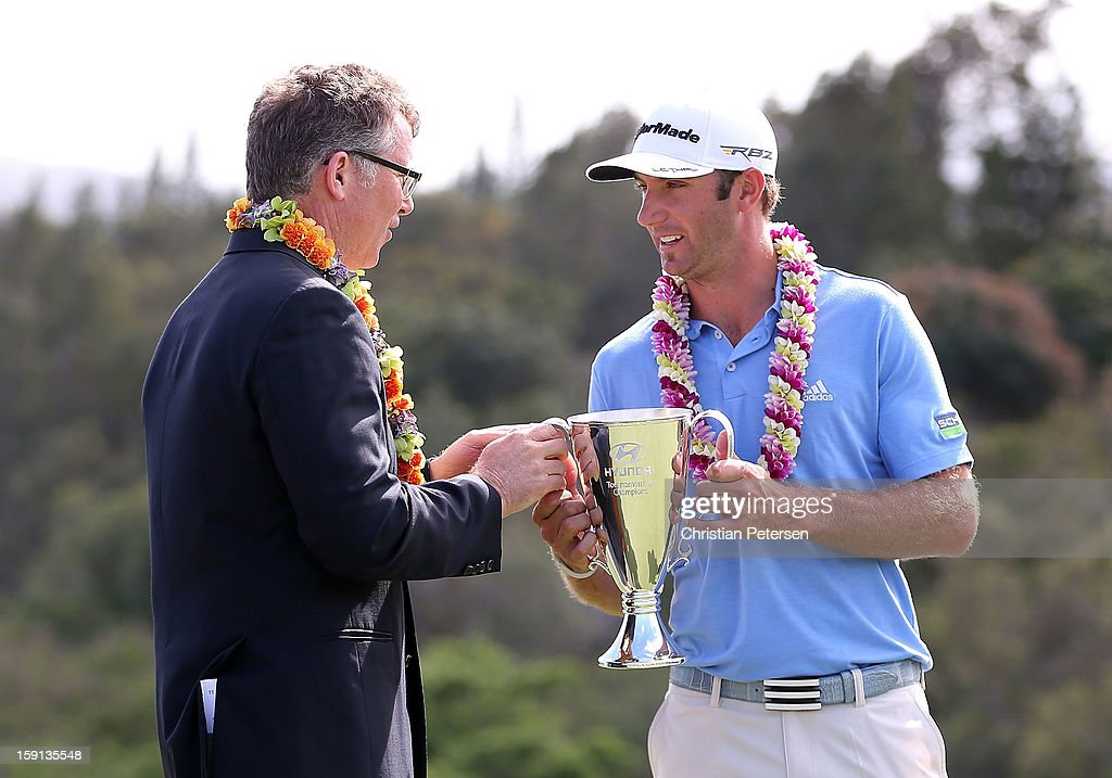 Dustin Johnson (R) is awarded the Hyundai Tournament of Champions Cup by Vice President of Marketing for Hyundai Motor America, Steve Shannon following the final round at the Plantation Course on January 8, 2013 in Kapalua, Hawaii.