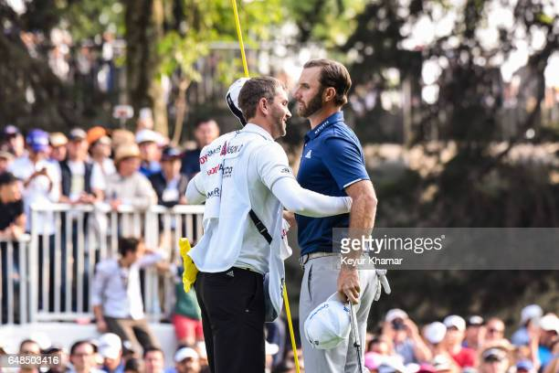 Dustin Johnson is hugged by caddie Austin Johnson after their victory on the 18th hole green during the final round of the World Golf...