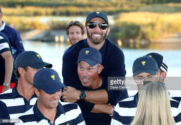 Dustin Johnson leaps onto the shoulders of Matt Kuchar during the official presentation ceremony during the final day singles matches matches in the...