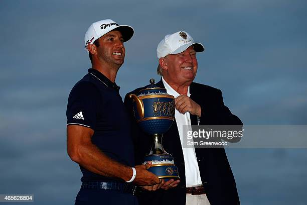 Dustin Johnson of the United States and Donald Trump pose with the Gene Sarazen Cup after winning the World Golf ChampionshipsCadillac Championship...