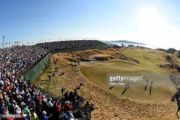 Dustin Johnson of the United States and Jason Day of Australia walk off the 18th green with their caddies during the final round of the 115th US Open...