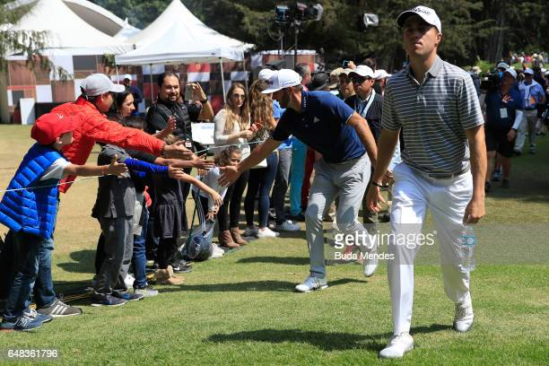 Dustin Johnson of the United States and Justin Thomas of the United States highfives fans as they walk to the eighth hole during the final round of...