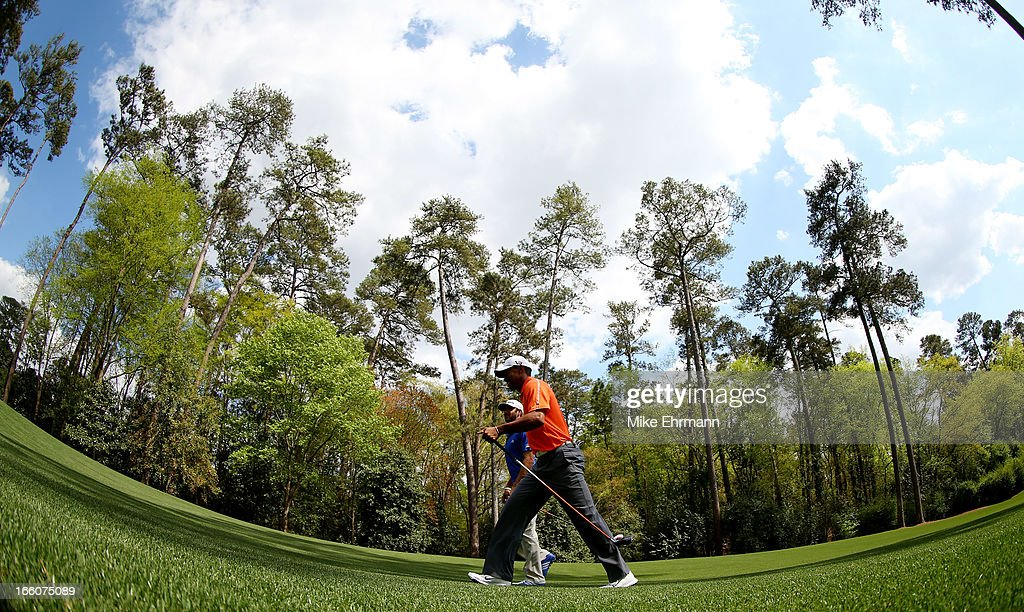 Dustin Johnson of the United States and Tiger Woods of the United States walk up the fairway during a practice round prior to the start of the 2013 Masters Tournament at Augusta National Golf Club on April 8, 2013 in Augusta, Georgia.