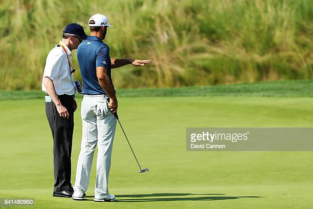 Dustin Johnson of the United States chats with a rules official on the fifth green during the final round of the US Open at Oakmont Country Club on...