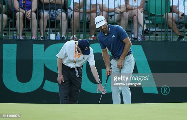 Dustin Johnson of the United States chats with a rules official behind the 16th green during the final round of the US Open at Oakmont Country Club...