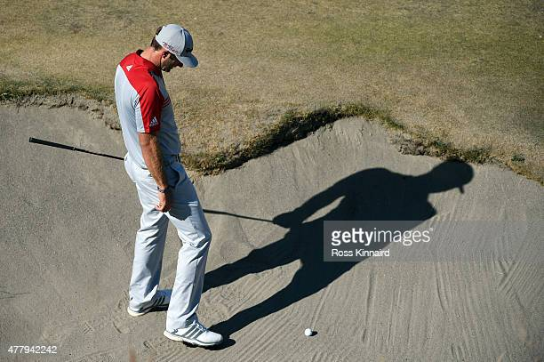 Dustin Johnson of the United States evaluates his shot from a bunker on the tenth hole during the third round of the 115th US Open Championship at...