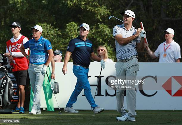 Dustin Johnson of the United States hits his tee shot on the fourth hole watched by Ryan Fox of New Zealand and Rickie Fowler of the United States...