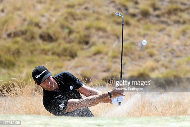 Dustin Johnson of the United States hits his third shot from a bunker on the third hole during the second round of the 115th US Open Championship at...