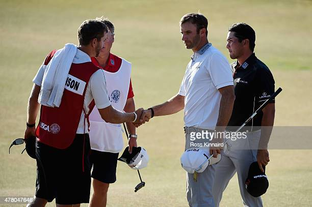 Dustin Johnson of the United States Jason Day of Australia caddie Colin Swatton and caddie Austin Johnson shake hands on the 18th green during the...