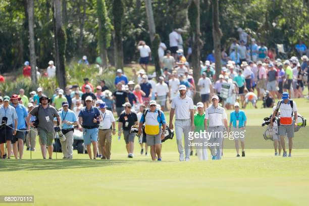 Dustin Johnson of the United States Justin Thomas of the United States and Rory McIlroy of Northern Ireland walk during the first round of THE...
