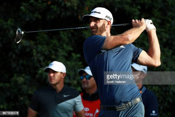 Dustin Johnson of the United States plays his shot from the 18th tee and Brooks Koepka of the United States looks on during the third round of the...