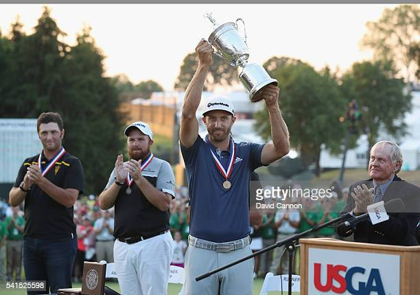 Dustin Johnson of the United States poses with the winner's trophy after winning the US Open as Shane Lowry of Ireland and Amateur Jon Rahm of Spain...